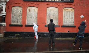 Three teenage boys kick a football against the wall of a run down boarded up pub.