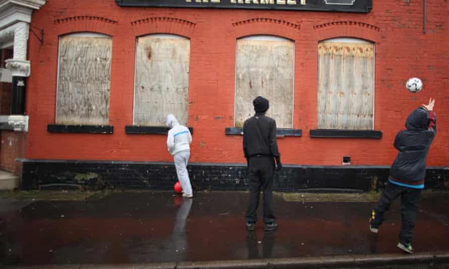 Three teenage boys kick a football against the wall of a run down boarded up pub.