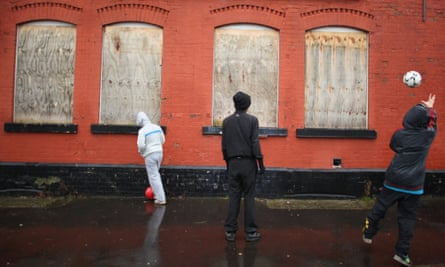 Youngsters play football up against a boarded-up pub