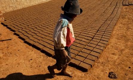 A child walks past hundreds of bricks drying in the sun in the brick-making neighbourhood of Cerro Blanco in Cochabamba, Bolivia