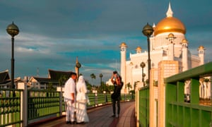 A newlywed couple have their photographs taken at the Sultan Omar Ali Saifuddin mosque in Bandar Seri Begawan, Brunei.