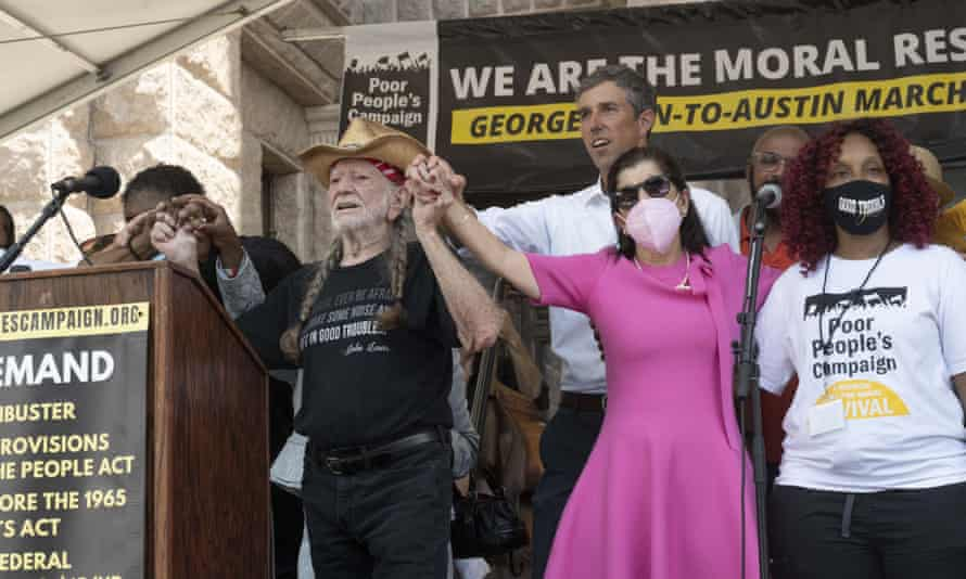 The singer Willie Nelson raises arms with Luci Baines Johnson at a rally in Austin, as Beto O'Rourke stands behind.