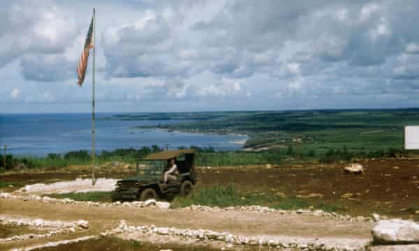 US soldier on hillside overlooking Tinian town.