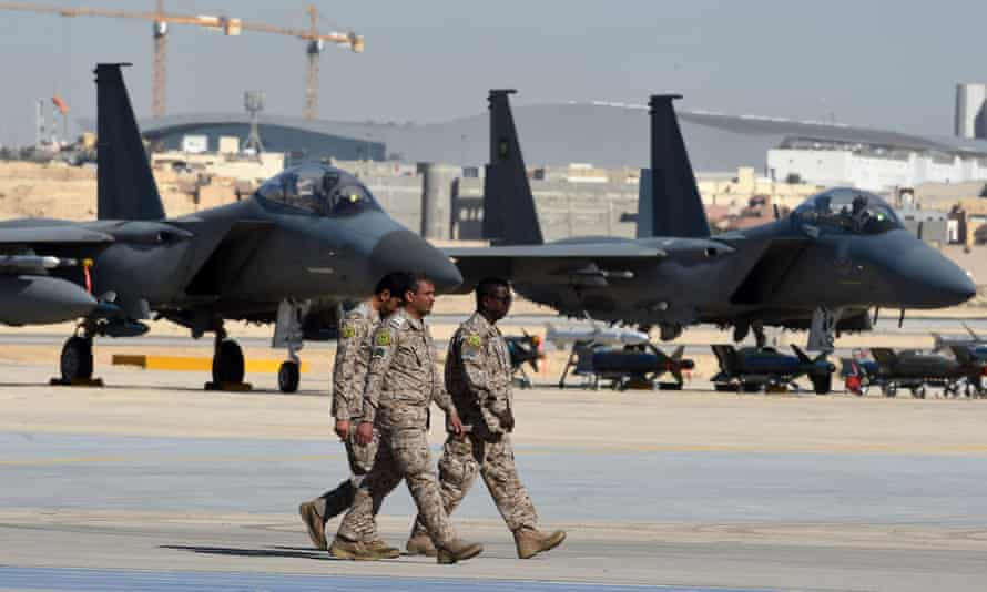 Saudi army officers walk past F-15 fighter jets
