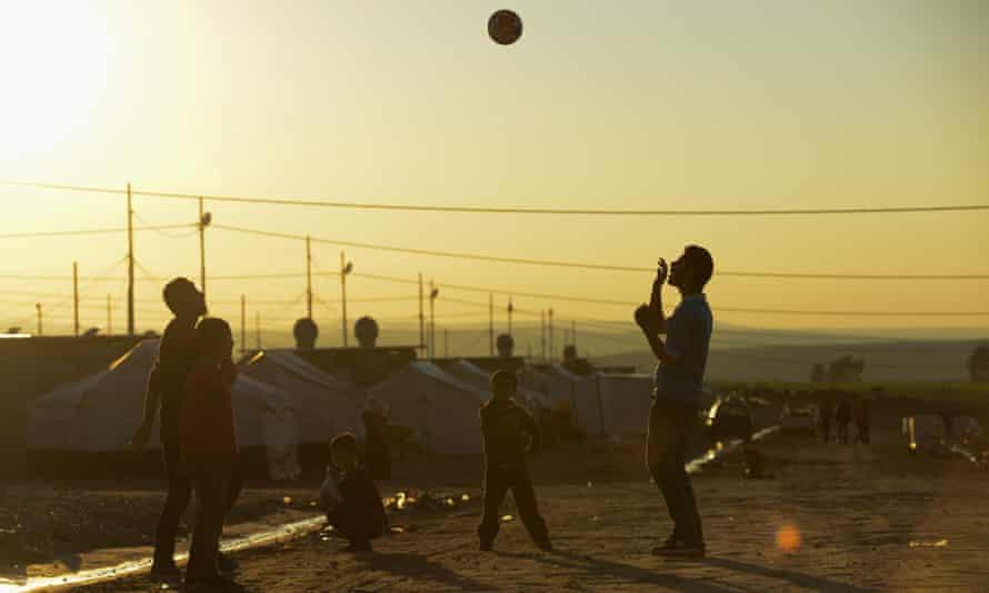 Refugees playing handball at sunset.