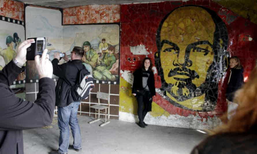 Tourists take photos in front of a mural of Vladimir Lenin in Skrunda-1, a former Soviet secret city in Latvia.