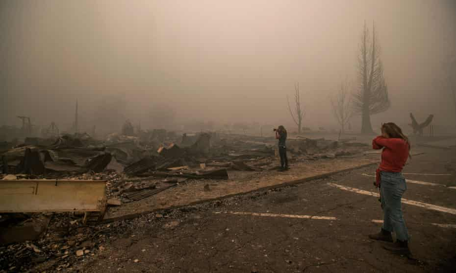 Tiffany Lozano, 44, right, covers her face from the smoke as her sister, Kelly Tan, 59, photographs what is left of Hunter's Hardware store and the Indian Valley Chamber of Commerce in Greenville.
