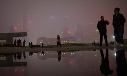 People walk on the Bund in front of the financial district of Pudong during a hazy night in downtown Shanghai