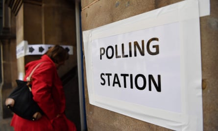 A woman enters a polling station to vote in local elections in London