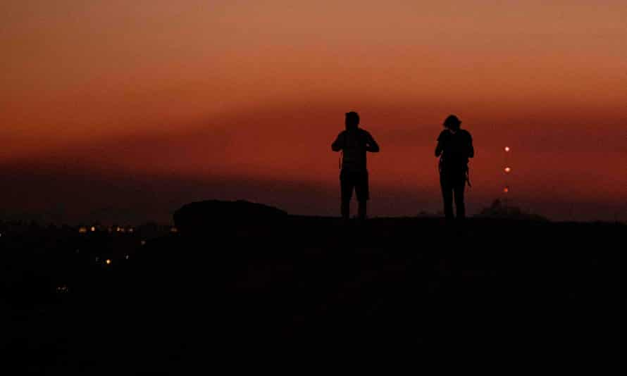 Hikers in LA's Griffith Park look west where a layer of smoke from the Saddleridge Fire hangs in the sky.