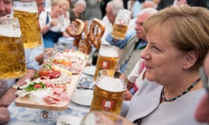German Chancellor Angela Merkel holds a glass of beer as she attends an election campaign event of the Christian Social Union (CSU), Bavarian sister party of her conservative Christian Democratic Union (CDU)
