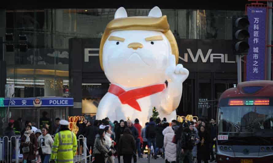 People look at a big dog sculpture resembling US President Donald Trump outside a shopping mall in Taiyuan, Shanxi Province, China.