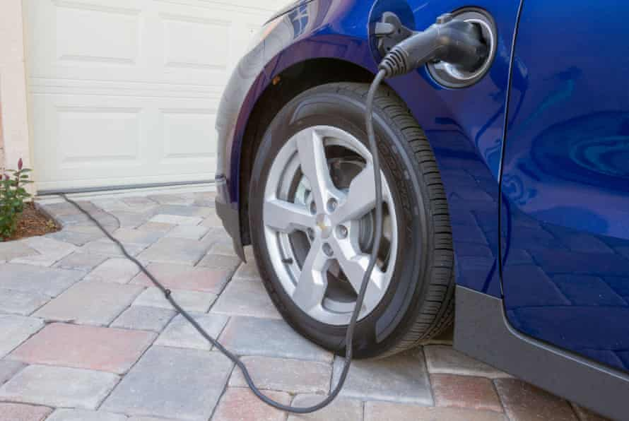 Plug-in hybrid electric car with connector plugged in and charging at home in a driveway