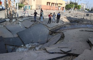 Palestinian youths take pictures with their smart phones of a huge crater on a main road in Gaza City on May 13, 2021 following continued Israeli airstrikes overnight on the Hamas-controlled Gaza Strip