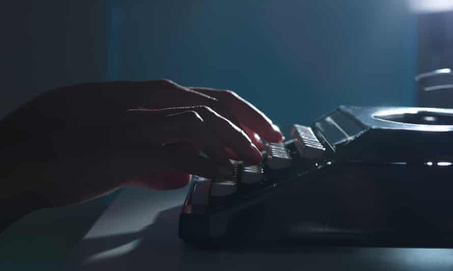 Close-up of woman using typewriter