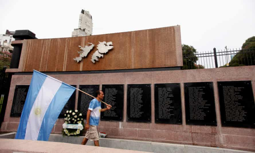 A man carries Argentina's national flag in front of the wall with names of those who died in the 1982 war between Britain and Argentina in the Falkland Islands.