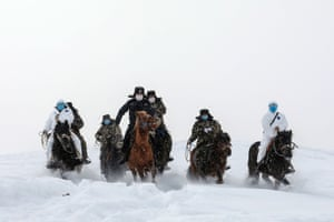 Altay, China. Police wearing protective face masks ride horse through the snow to reach residents in remote areas in the Xinjiang region as part of an effort to raise awareness about the coronavirus