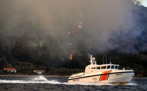 A Turkish coastguard boat passes by a wildfire burning in the Milas district of Mugla