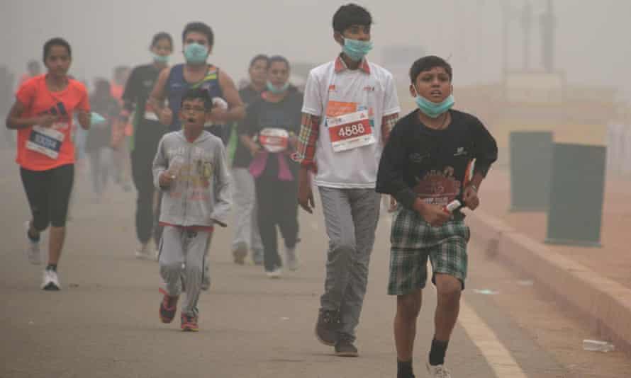 Indian children run in smog