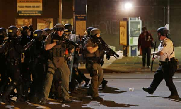 Police in riot gear fall back after arresting a protester for violating a curfew in Baltimore last Friday.