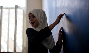 A girl writes on the blackboard at a school in Kandahar, Afghanistan