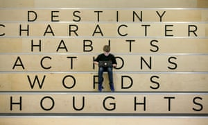 boy sitting on stands with encouraging words on them