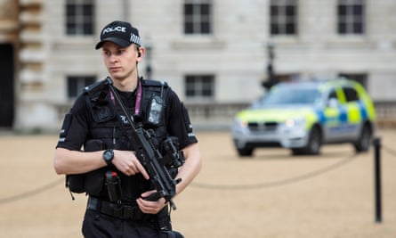 An armed police officer patrols in Horse Guards Parade, central London