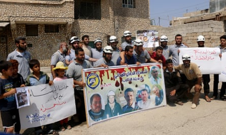 Demonstrators hold placards and photos during a White Helmets protest in the Etarib district of Idlib, Syria.
