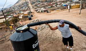 A water distribution worker fills a tank in Peru.