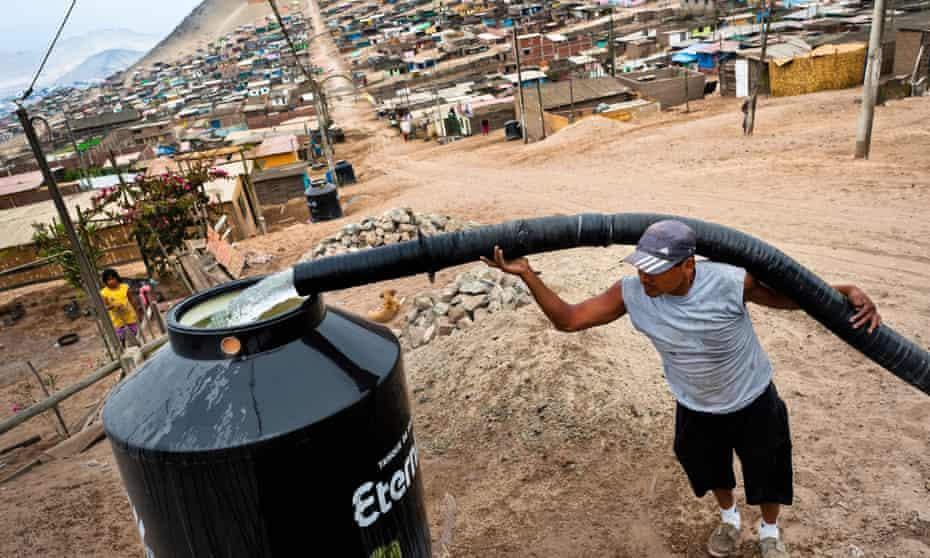 A water distribution worker fills a tank in Peru.