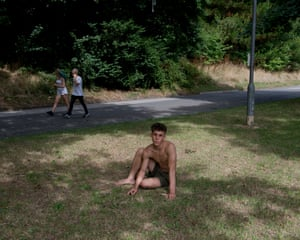Ison, from Cornwall, sitting in the shade in a park with a bare chest and legs