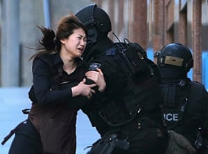 A hostage runs to an armed tactical response police officers for safety after she escaped from a cafe under siege at Martin Place in Sydney