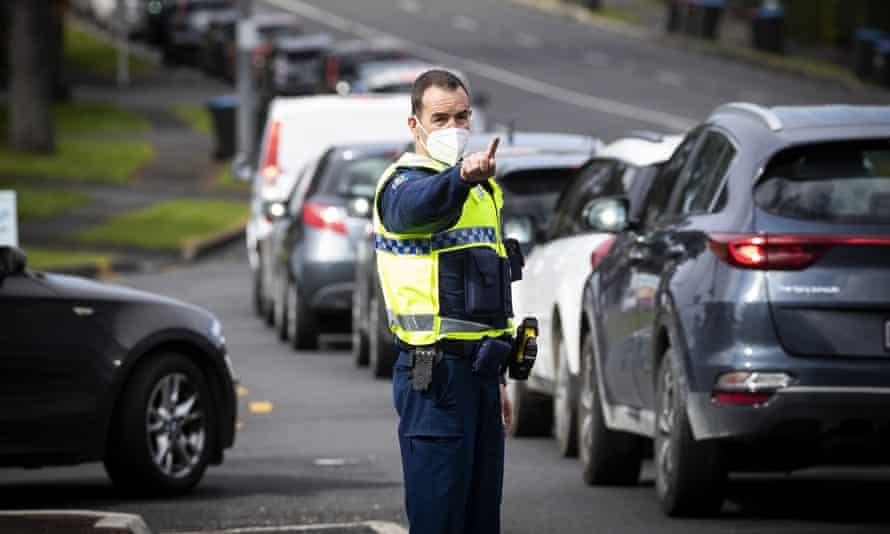 A police officer controls a line of vehicles waiting for Covid-19 testing in Auckland, New Zealand