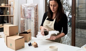 Focused woman packing clay utensil into paper and carton boxes for further sale.