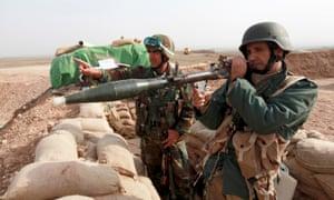 Kurdish peshmerga soldiers aim guns across a wall of sandbags