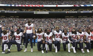 Houston Texans players kneel and stand during the singing of the national anthem in October