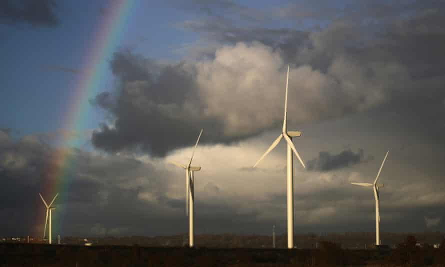 A rainbow appears behind wind turbines