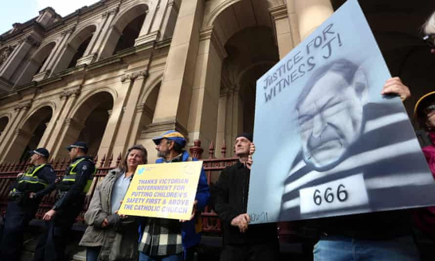Protesters hold placards outside the court building as Cardinal George Pell is escorted into the supreme court of Victoria in Melbourne