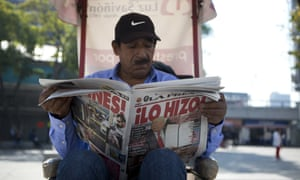A man in Mexico City reads a newspaper whose front page declares 'He did it!', on the day Trump signed an executive order to jumpstart the wall.