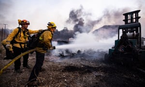 Firefighters work at extinguishing the Tick fire in a factory near Santa Clarita, California, 24 October 2019.