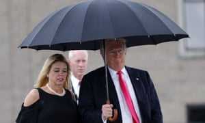 Republican presidential candidate Donald Trump walks in the rain with Florida Attorney General Pam Bondi, who is among the Republican attorneys general that received donations from the fossil fuel industry and sued to halt the Clean Power Plan.