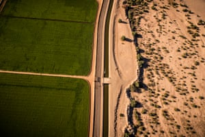 Green US farmland separated from the dry desert by the USA/Mexican border and an irrigation canal