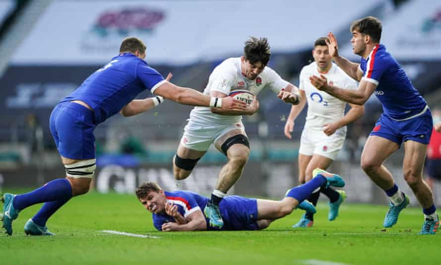 Tom Curry leaps over the challenge of Antoine Dupont during a man-of-the-match display for England against France