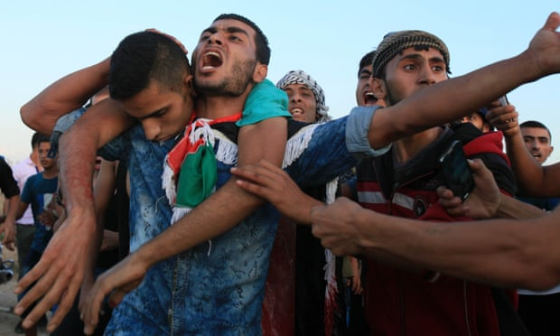 09 Oct 2015, Gaza, Gaza Strip --- Palestinians carry a wounded protester, who was shot by Israeli troops, during clashes near the Israeli border fence in northeast Gaza October 9, 2015.