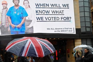A pedestrians pass a billboard with a Brexit-related campaign slogan in Leicester Square in London.