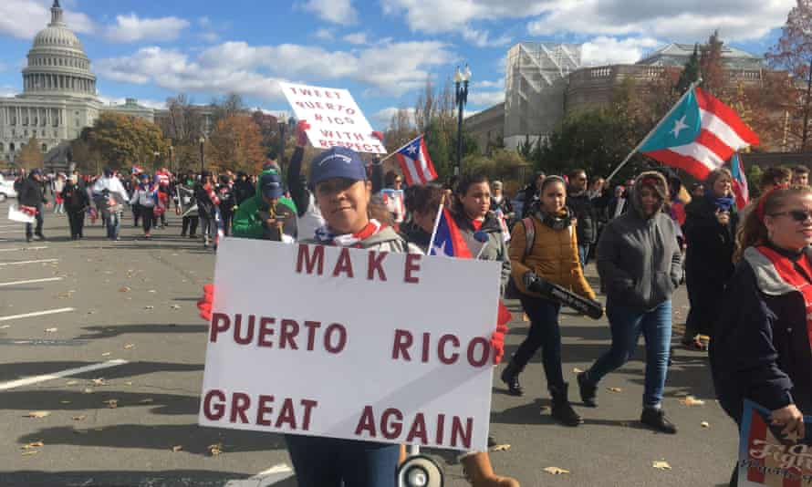 People carry signs during a 19 November 2017 protest for Puerto Rico in Washington DC.