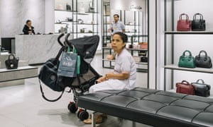 A nanny nurses a baby while the parents are shopping in Charles & Keith in Plaza Indonesia.