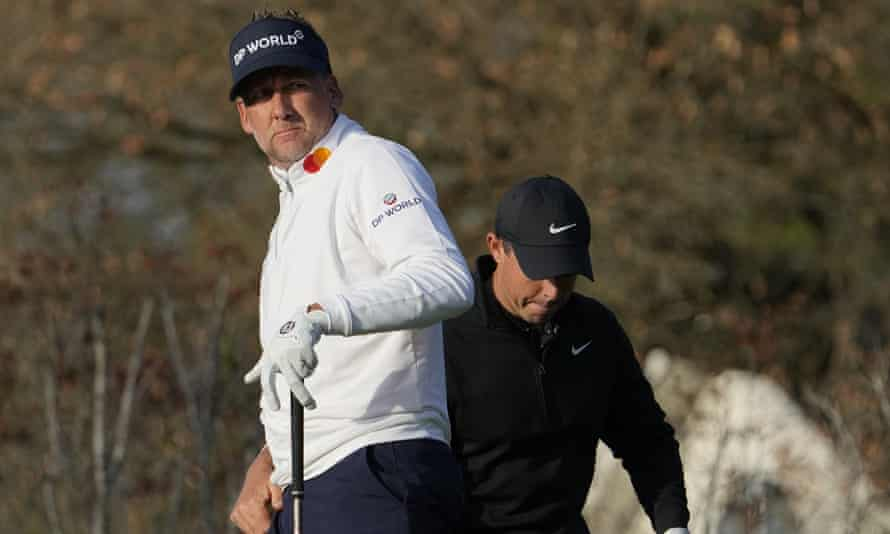 Ian Poulter watches his shot as Rory McIlroy readies his in the background at the WGC Match Play in Texas.