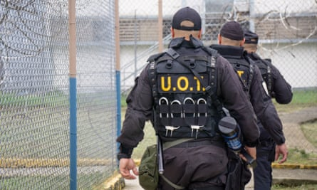 A tactical unit of three officers walks around barbwire fences in the Bayamón correctional complex.