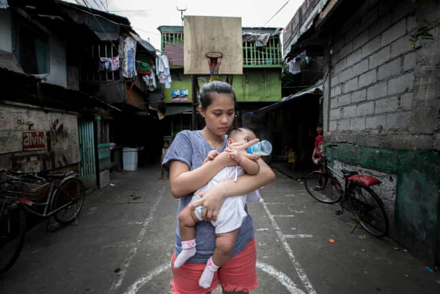 Trixia, 19, bottle feeds her four month-old daughter near her home in a deprived community in Navotas, Metro Manila, the Philippines.